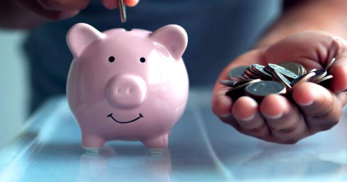 Putting coins into piggy bank retirement plan